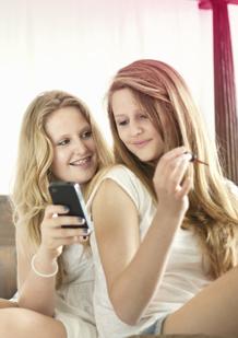תמונה של שתי נערות צעירות. אחת אוחזת במכשיר סלולארי והשניה מורחת לק על ציפורניה. התמונה ממחישה כי השינויים הקורים בגוף הם נורמליים וכי אפשר לדבר על כך עם החברים או ההורים.