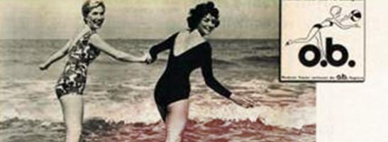 תמונה של 2 נשים בבגד ים, אוחזות יד ביד. התמונה מיושנת וממחישה את המהפכה הנשית. לוגו  o.b. הישן מוצג על גבי התמונה.